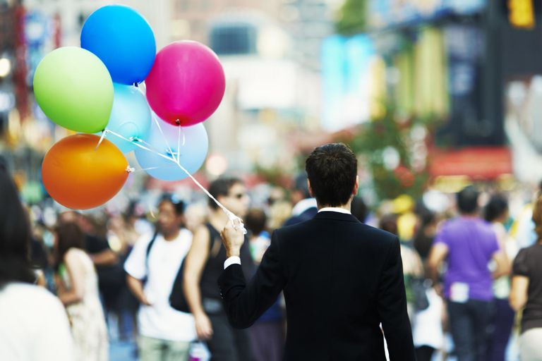 Businessman holding balloons in crowd