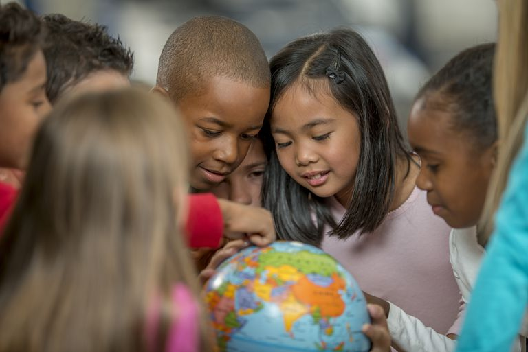 Group of young students studying a globe.