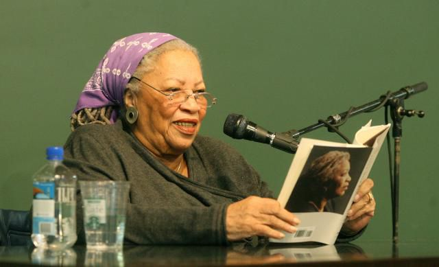 Toni Morrison giving a reading in front of a green background.