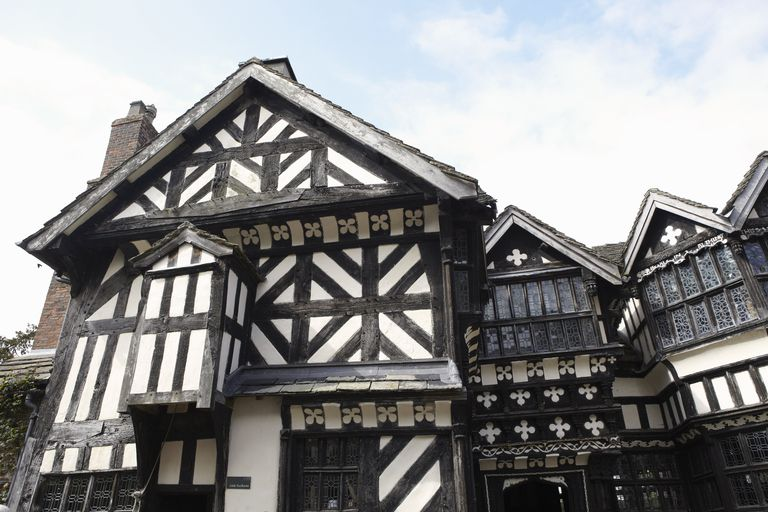 Half-timbered 16th century house in England with large brown wooden beams poking through the white siding