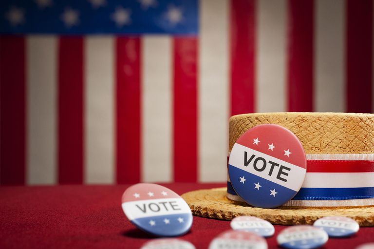election vote buttons next to a straw hat