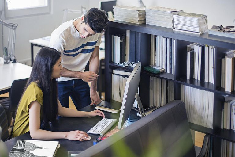 Two young people working together in office at computer