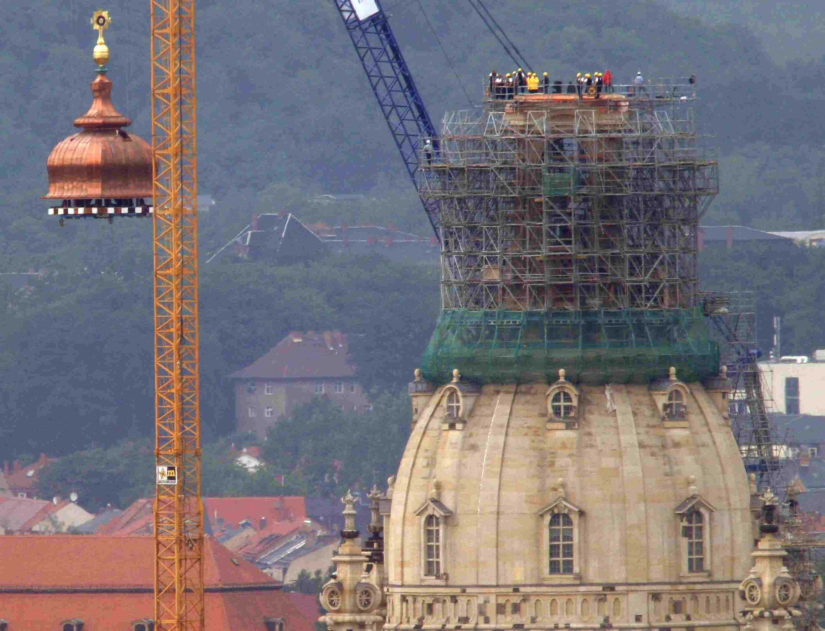 A crane lifts the copper cupola and golden cross to the top of the reconstructed Frauenkirche in Dresden, Germany