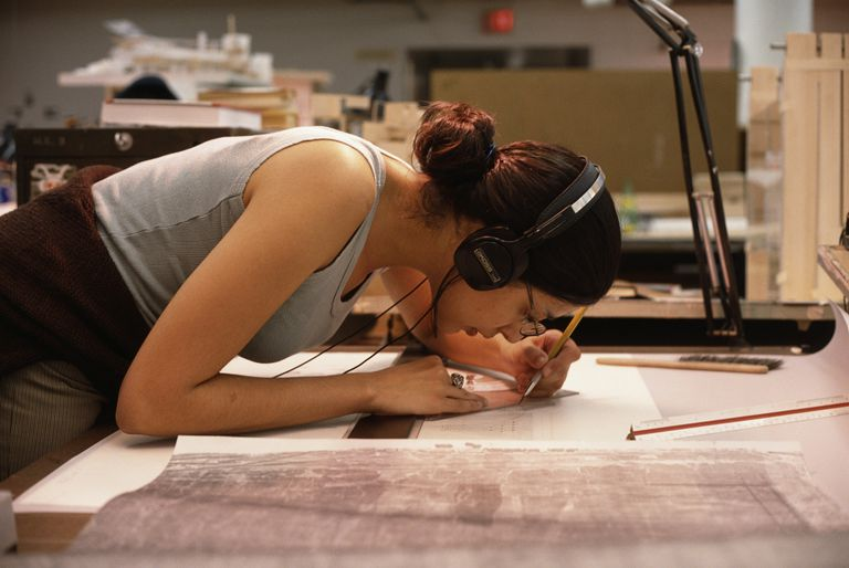 Female student architect in sleevless top, leaning over drafting table to draw plans