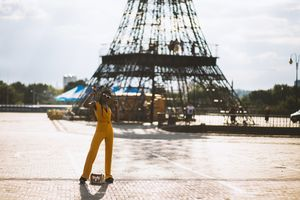 Young woman standing in front of the Eiffel Tower.