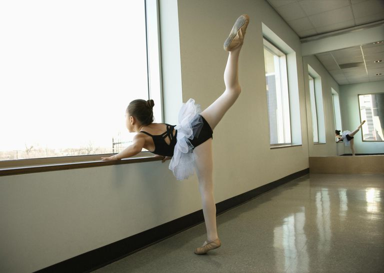 Girl practicing ballet by window