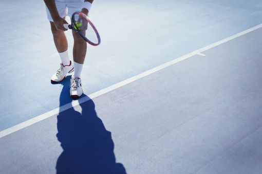 Young male tennis player preparing to serve the ball on sunny blue tennis court