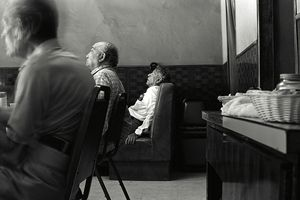 An elderly man sleeps in a cafe