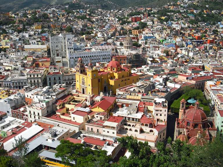 Aerial view of a busy town in Mexico surrounded by mountains and trees.