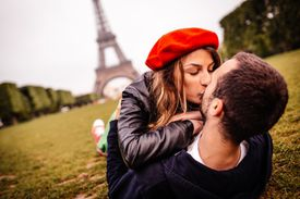 A couple kisses on the lawn by the Eiffel Tower