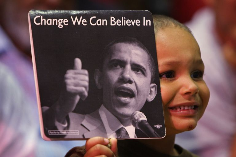 "Boy holding up Obama ""Change We Can Believe In"" sign"