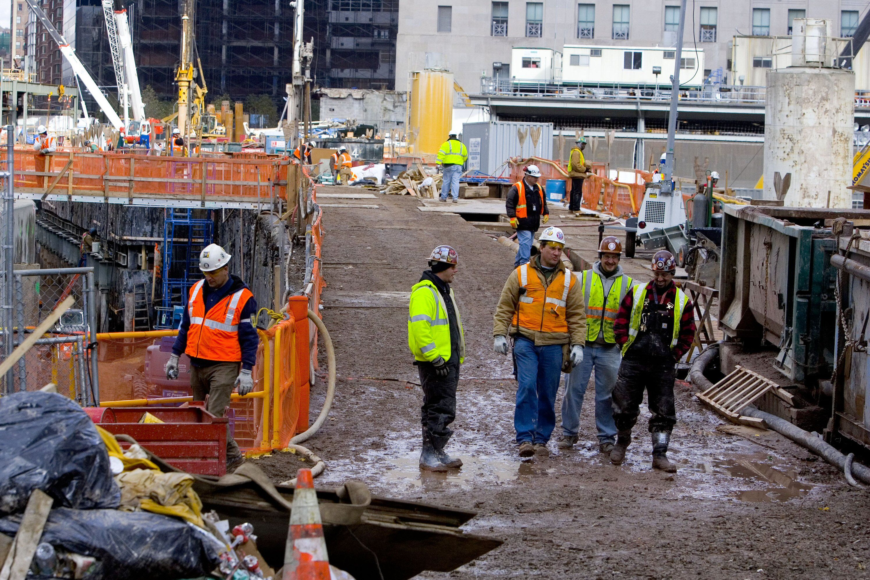 close up of muddy construction site with workers in brightly colored vests and hard hats