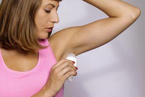 Young woman applying underarm deodorant