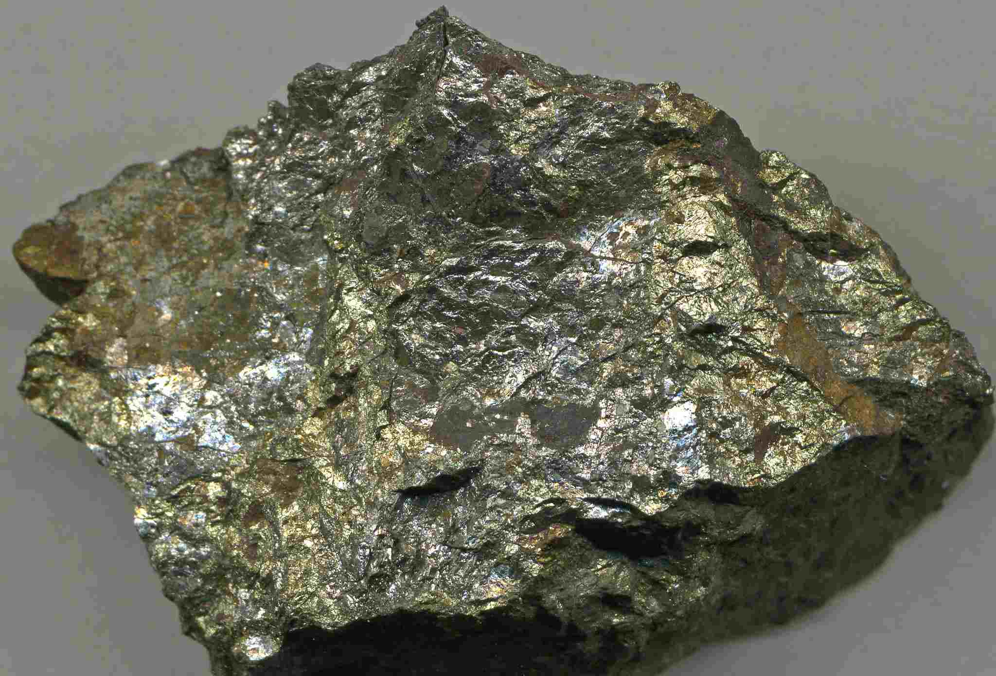 Chalcopyrite chunk close up on a gray background.