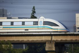 A Shanghai Maglev traveling through a Pudong neighborhood at high speed