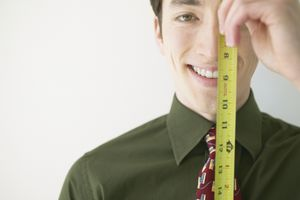 Man holding measuring tape in front of his face