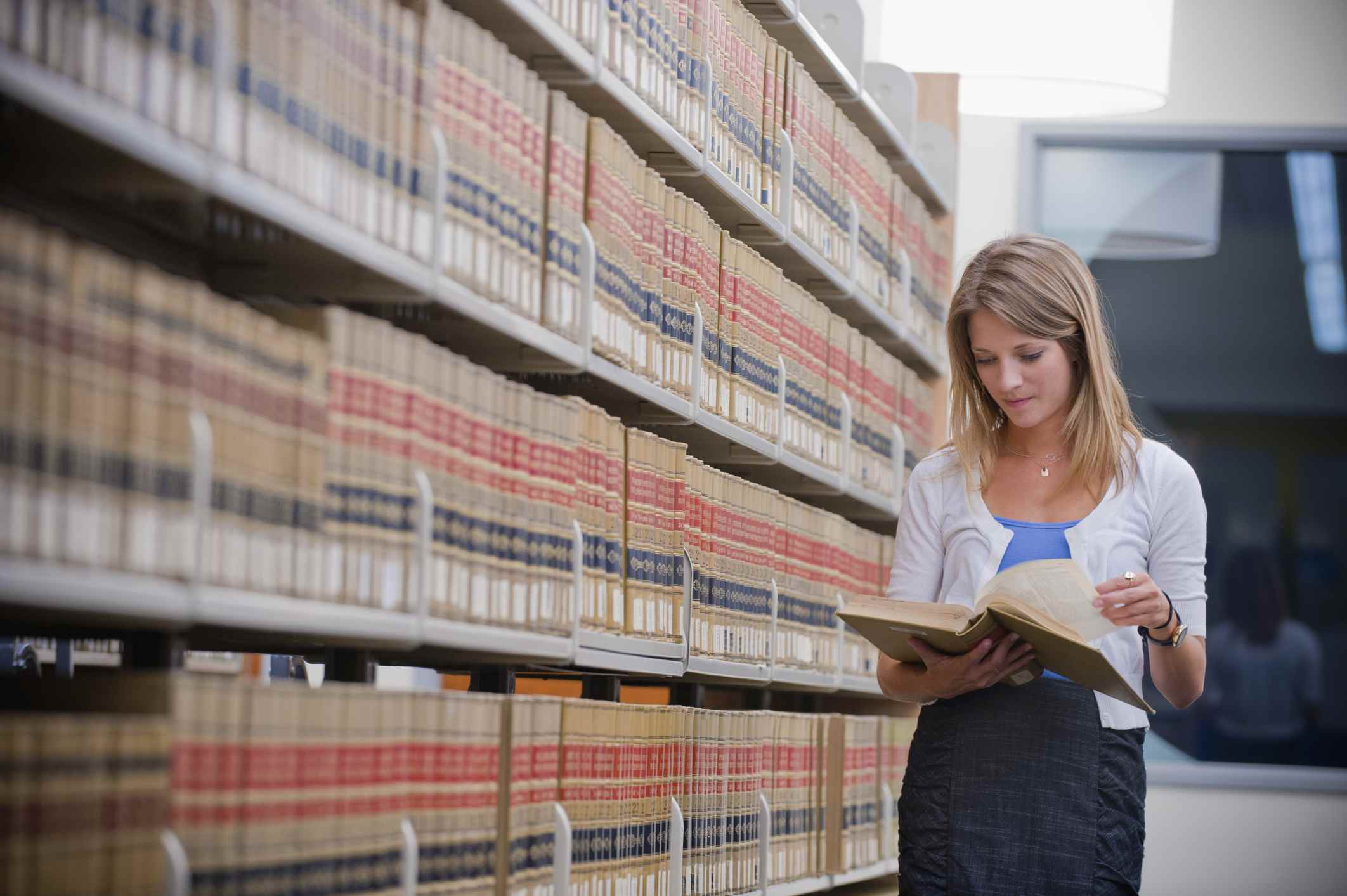 Young woman looking through law books