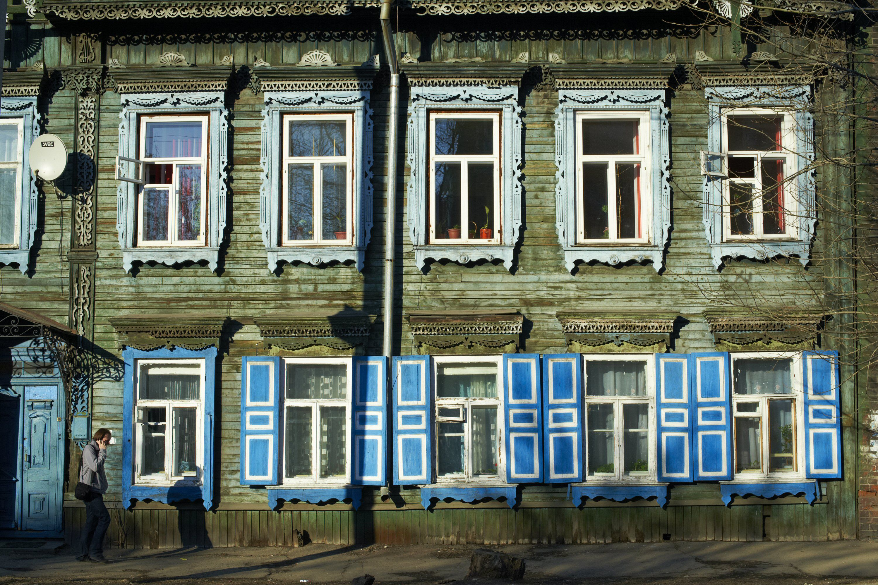Two story wooden house with ornate wooden window trimming and colorful blue shutters