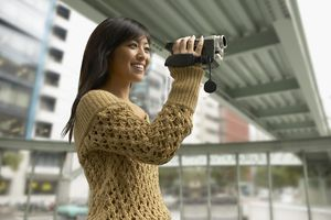 Teenage Girl Stands Below an Overpass Filming With a Digital Camcorder