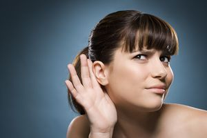 Woman putting hand to her ear