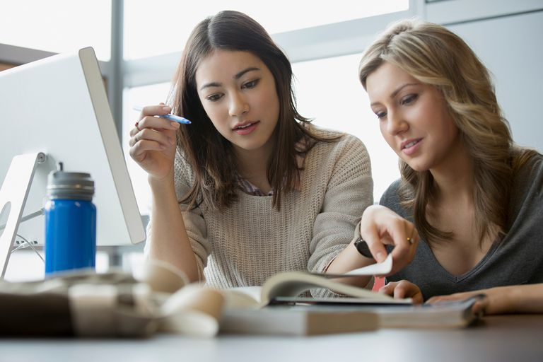 A woman helping another woman study