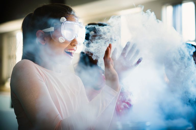 Girl in safety goggles laughing in a cloud of steam.