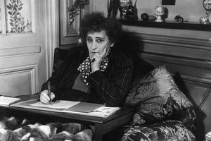 Black-and-white photo of Colette sitting at a writing desk with her pen in hand