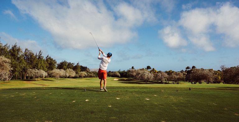 man in white tshirt playing golf
