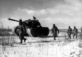 A column of troops and armor of the 1st Marine Division move through communist Chinese lines during their successful breakout from the Chosin Reservoir in North Korea.