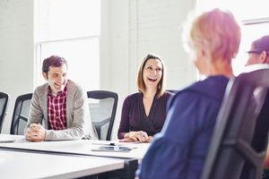 Adults laughing in conference room