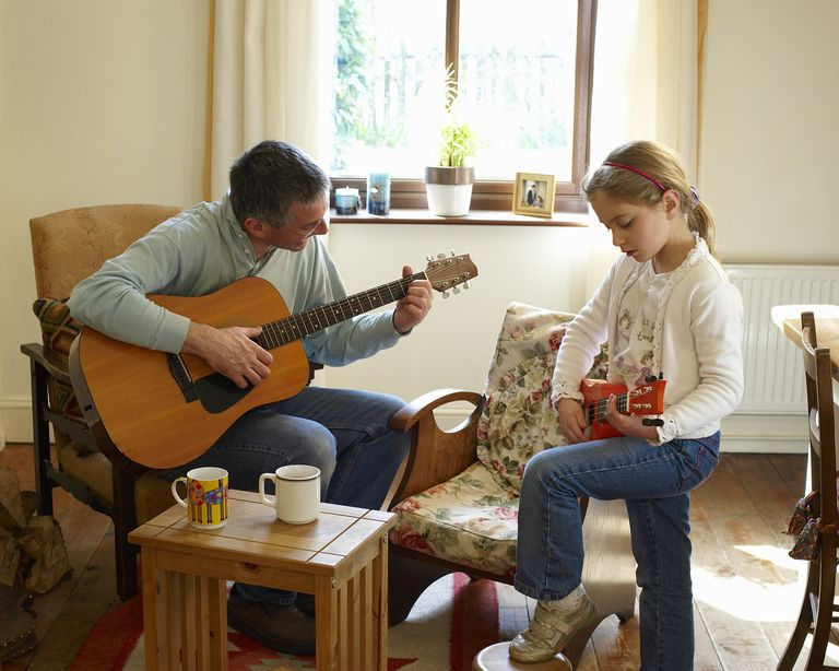 man playing guitar with child