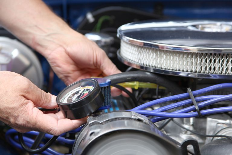 adjusting a carburetor while reading vacuum gauge