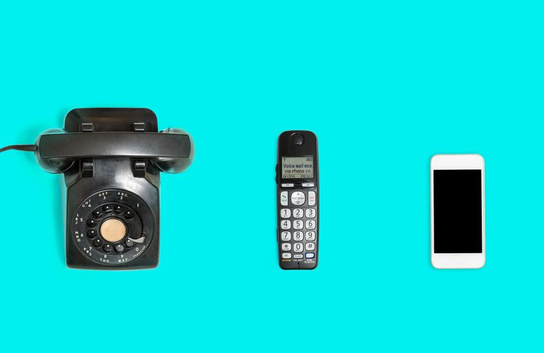 Aerial Shot Of Various Phones From Different Eras Over Blue Background