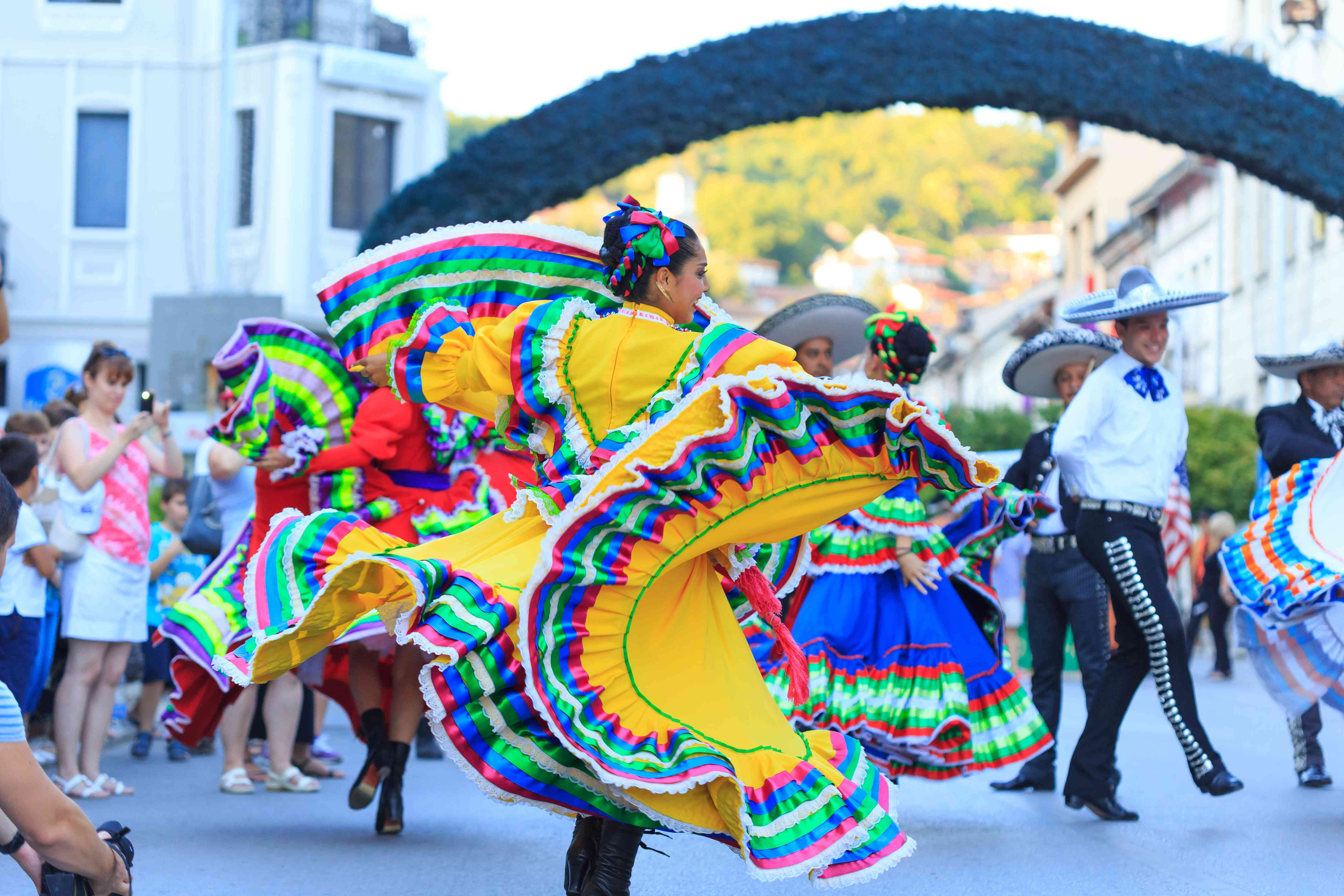Performers in traditional costumes from Mexican group dancing on street