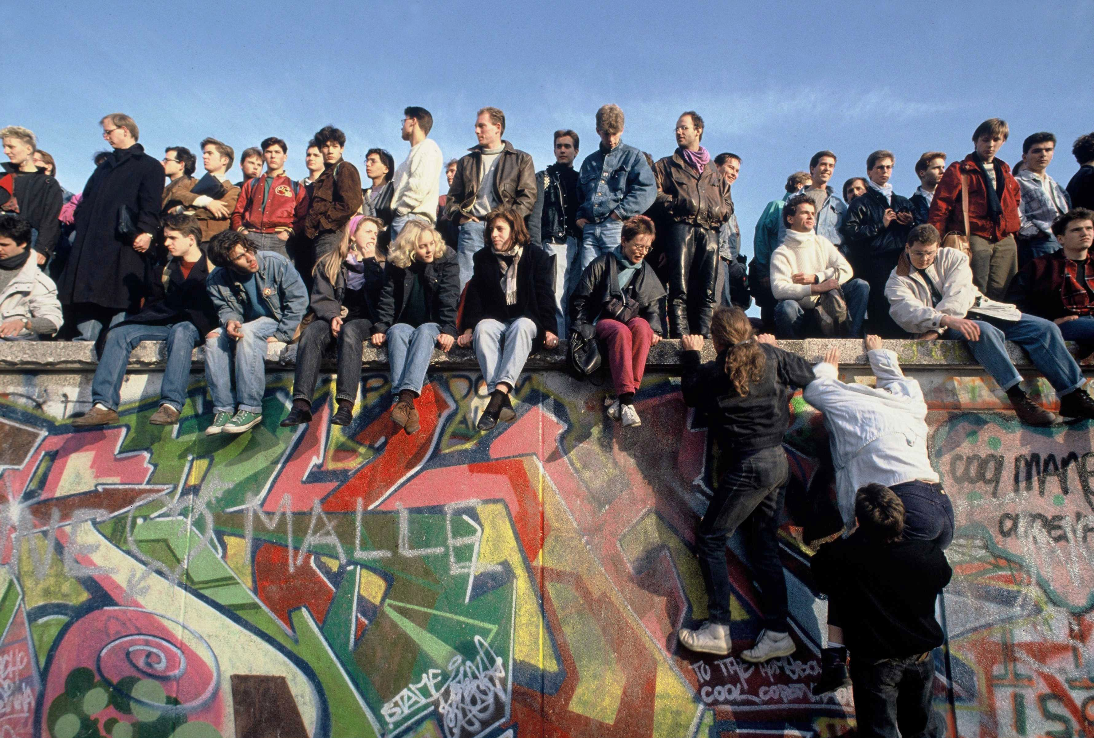 People climb onto the Berlin Wall on November 10th, 1989 in celebration.