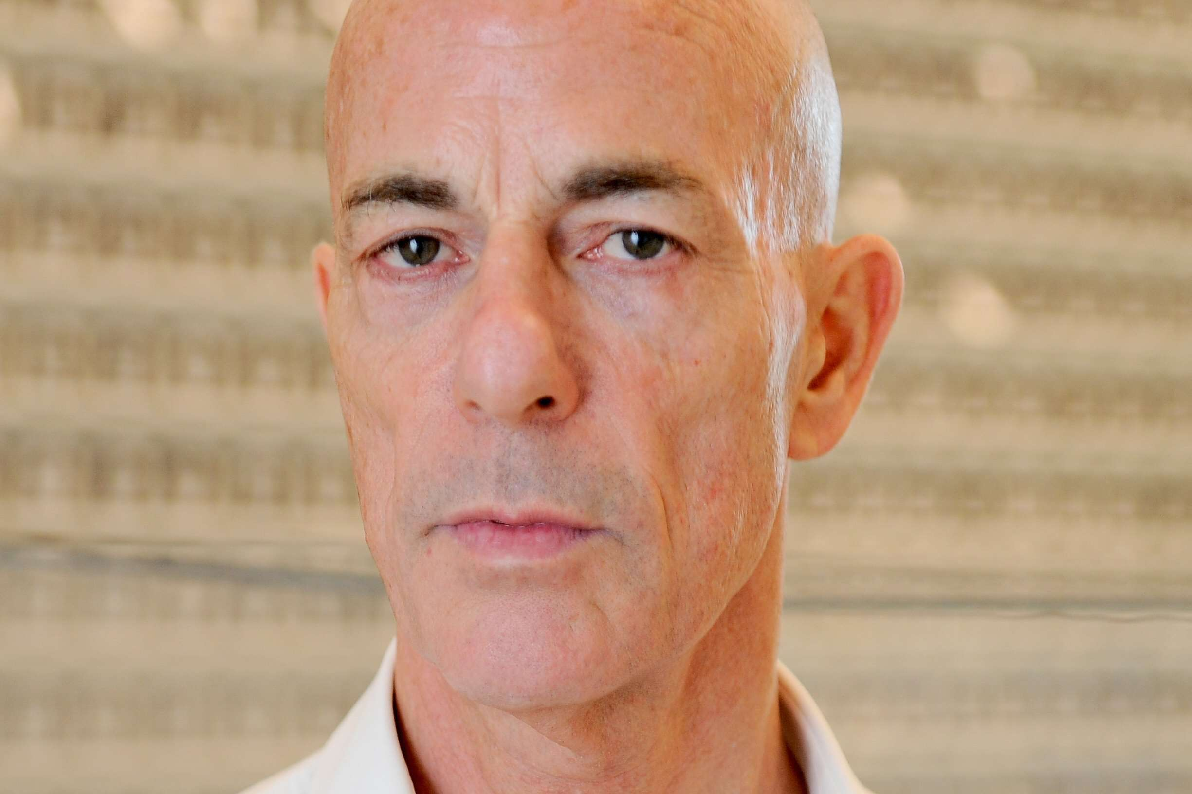 bald white man with dark eyebrows and intensive stare toward the camera