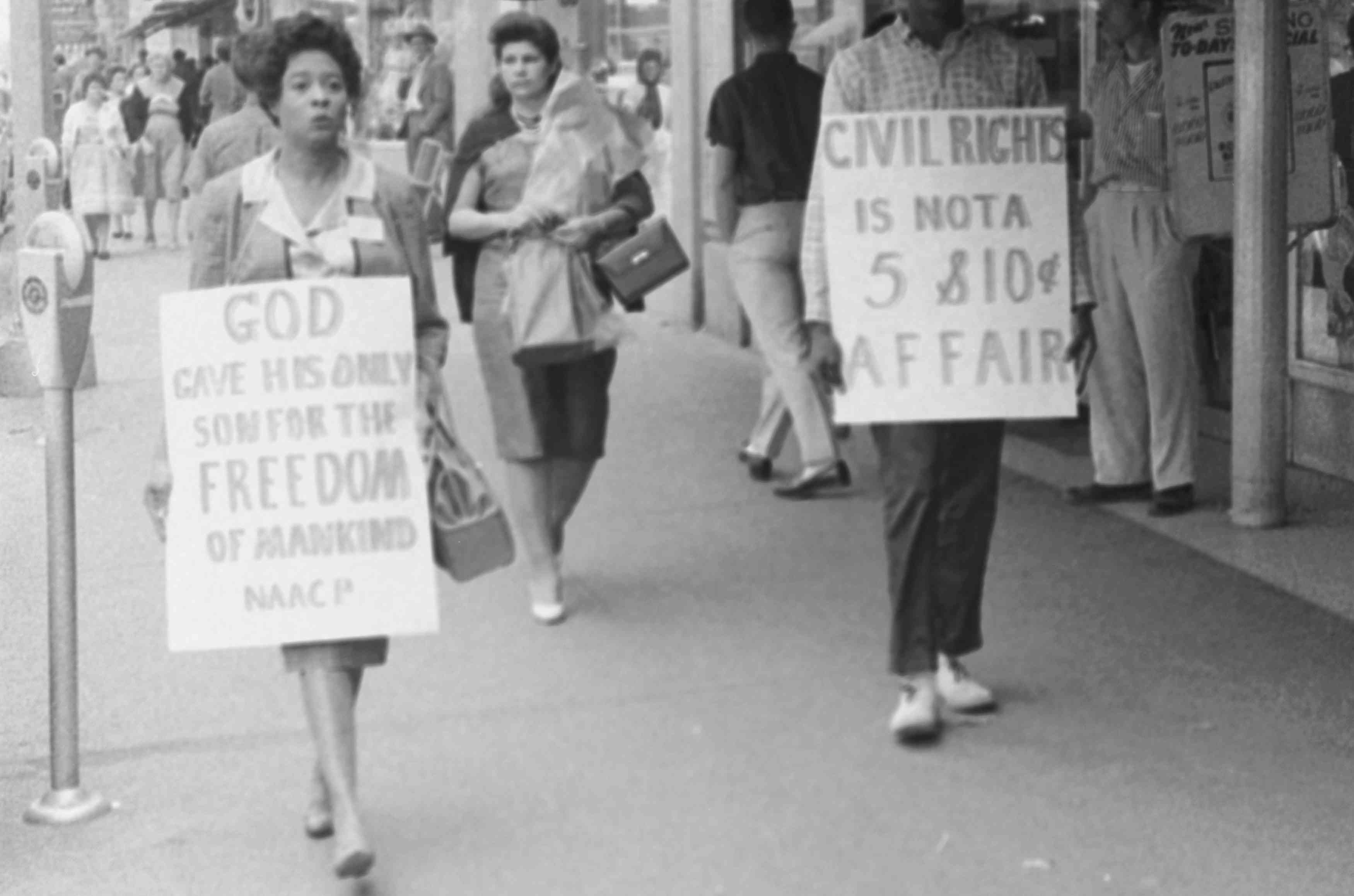 Daisy Bates holding a sign that reads