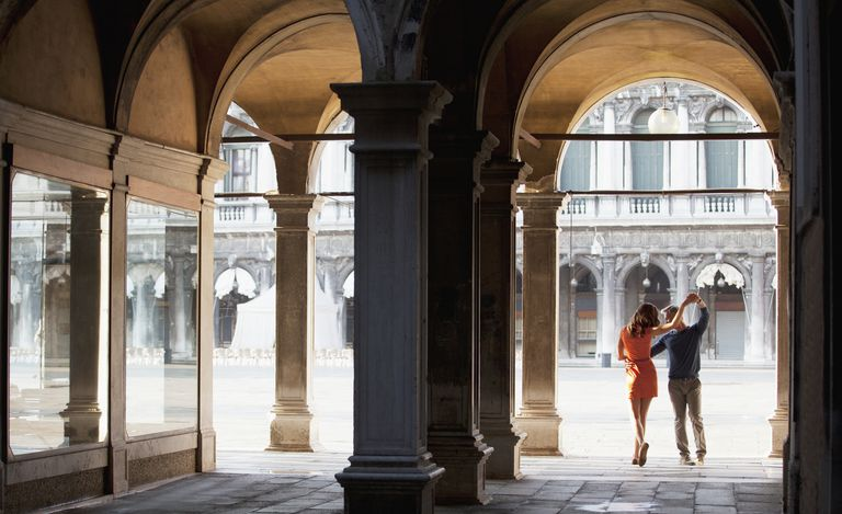 Couple dancing in archway in Venice
