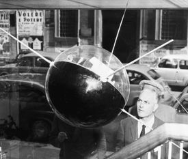 A man observes a model of Russia's Sputnik I, on display in a Rome department store.