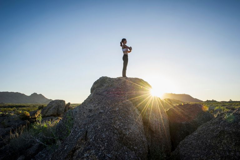Woman in prayer position standing on a rock with the sun rising