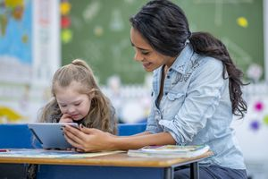 A teacher showing a tablet to a young girl with Down Syndrome
