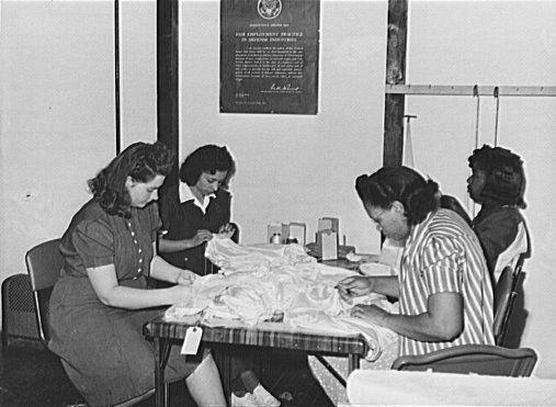Four multiethnic women sew parachutes for the World War II war effort