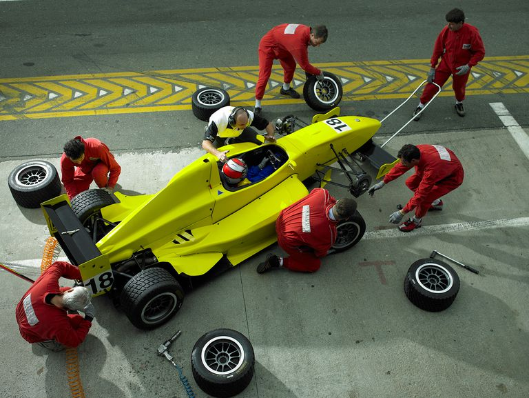 Pit crew changing tires on Formula 1 race car, elevated view.