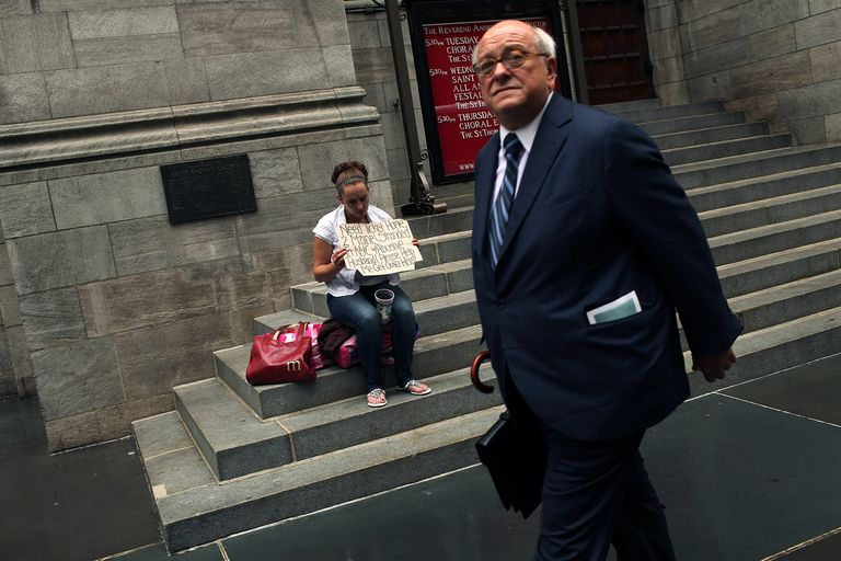 A businessman walks by a homeless woman holding a card requesting money.