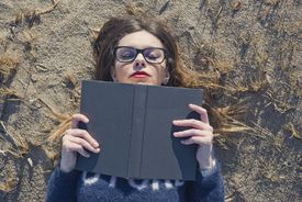 Shot of an young woman reading a book while lying outside on the beach