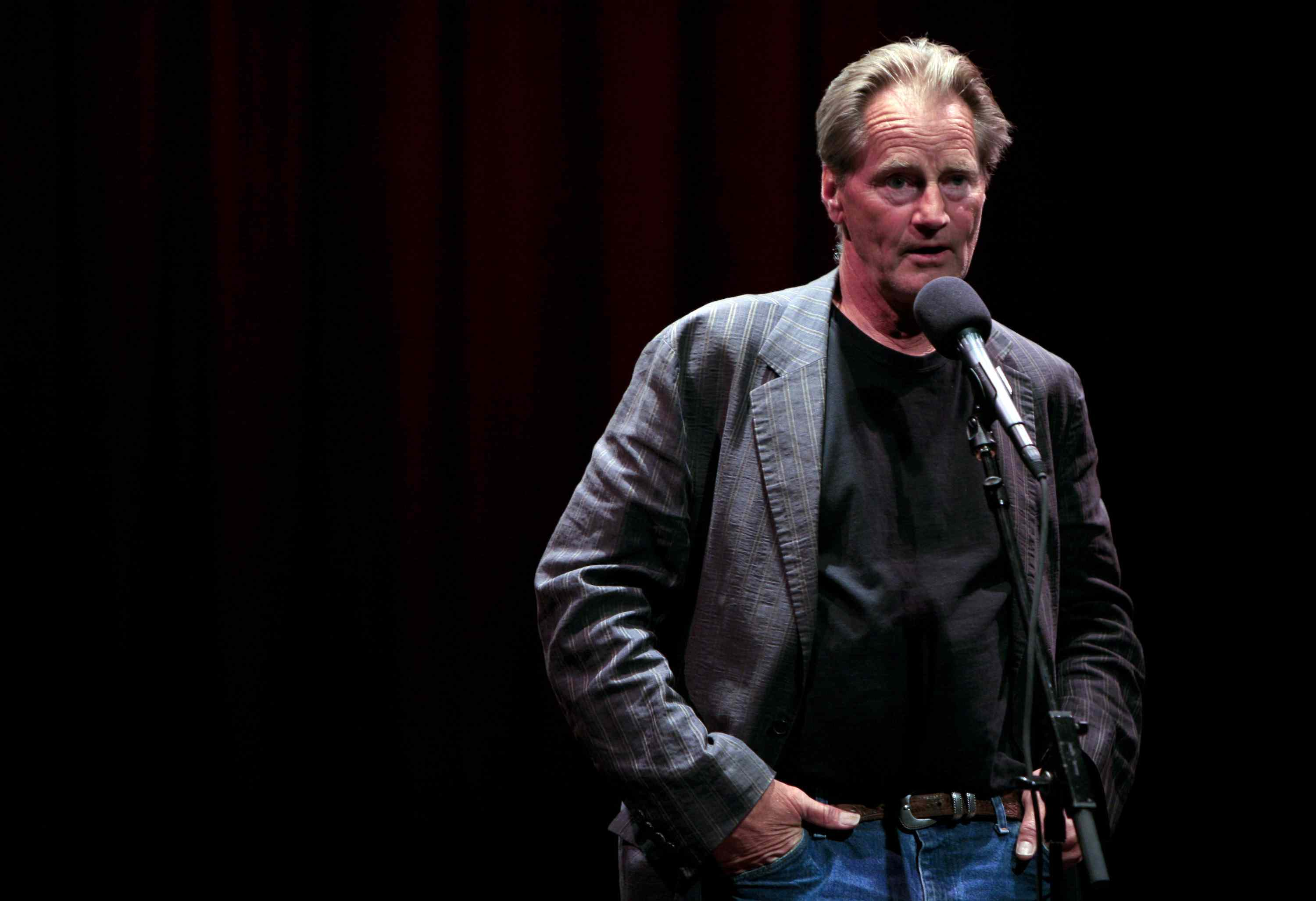 Sam Shepard, standing with hands in pockets, at a microphone