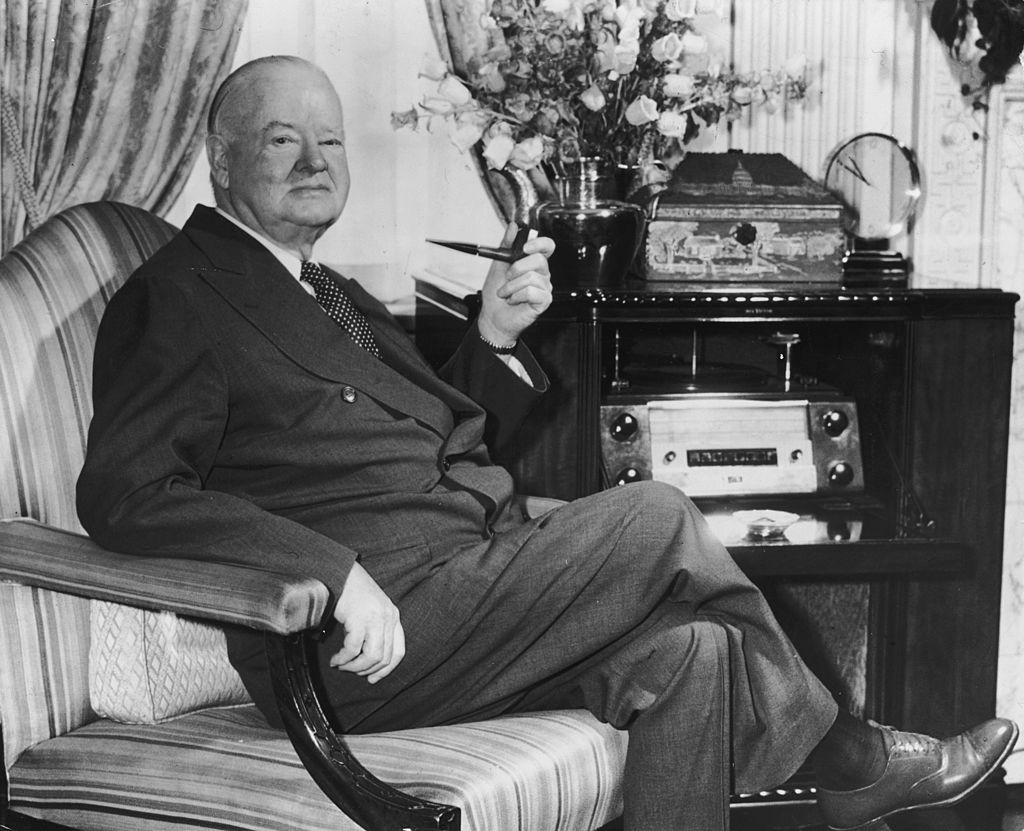 circa 1962: Portrait of former American president Herbert Hoover (1874 - 1964) seated in an armchair with a pipe in his suite at the Waldorf Towers, New York City.
