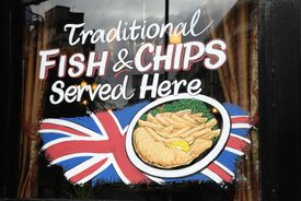 Traditional Fish and Chips sign in the window of a London pub
