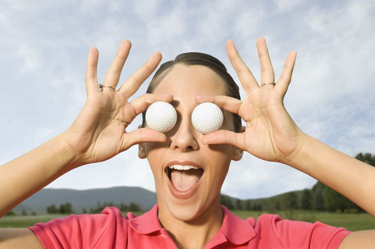 Golfer covers her eyes with golf balls