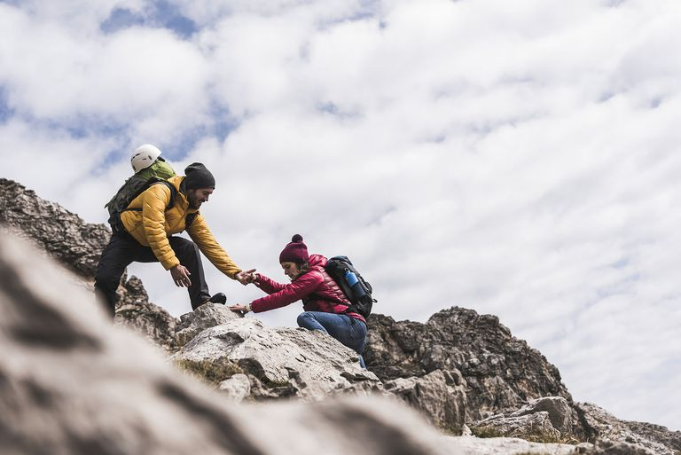 Man Helping Woman Climbing up Rock